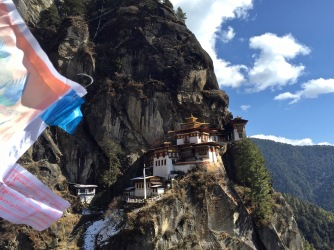 Prayer flags blowing along the stairs towards Taktsang
